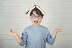 Glückliches und lächelndes Kind mit Buch auf Kopf lizenzfreies stockfoto