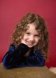 Glückliches und lachendes Chirstmas-Kind, roter Feiertags-Winter-Hintergrund Stockbilder