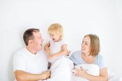Glückliches und liebevolles Familienmorgenkonzept Nette Eltern im Sleepwear, der Spaß mit ihrer Tochter auf dem Bett hat Familien Stockbilder