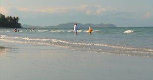 Glückliches und sorgloses Leute-Spiel durch das Meer, Schwimmen Kinder und Erwachsene spielen durch das Meer auf einem tropischen stock video footage