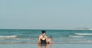 Glückliches und sorgloses Mutter-und Sohn-Spiel durch das Meer, nehmen ein Sonnenbad, schwimmen Kinder und Erwachsene spielen dur stock video footage