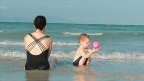 Glückliches und sorgloses Mutter-und Sohn-Spiel durch das Meer, nehmen ein Sonnenbad, schwimmen Kinder und Erwachsene spielen dur stock footage