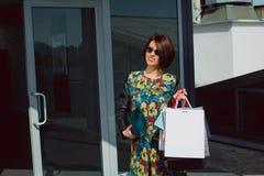 Glückliches und stilvolles Mädchen kommt das Einkaufszentrum und aus das holdi heraus Stockfotos