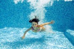 Glückliches Unterwasserkind springt zum Swimmingpool Stockbild