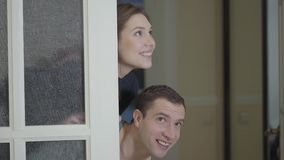 Glückliches verheiratetes Paar kontrolliert ein eben gekauftes Haus oder eine Wohnung Lächelndes Mädchen und Mann, die aus der Tü stock video footage