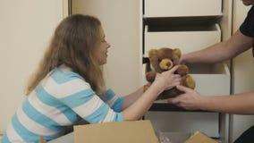 Glückliches verheiratetes Paar packt Sachen nach Verlegung in einem neuen Haus aus stock video