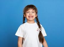 Glückliches verlorenes Zahnmädchenporträt, Studiotrieb auf blauem Hintergrund Lizenzfreies Stockbild