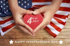 Glückliches 4. von Juli-Zeichen auf Herzen an der Leutehand Lizenzfreie Stockbilder
