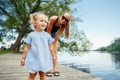 Glückliches weißes kaukasisches Mutter- und Tochterkind, das Spaß draußen hat Stockbild