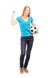 Glückliches weibliches Gebläse, das einen Fußball und ein Gestikulieren anhält Lizenzfreie Stockbilder