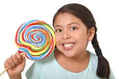 Glückliches weibliches Kind, das große Lutschersüßigkeit im Ausdruck des fröhlichen Gesichts in der Kinderliebe für süßes Konzept Stockfotos