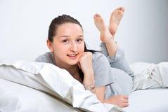 Glückliches weibliches Lügen auf Bett Stockbild