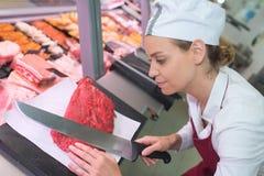 Glückliches weibliches Metzgerausschnittfleisch am Schlächtereizähler stockfotos