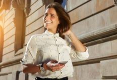 Glückliches weibliches Modell, das an ihrem intelligenten Telefon beim Gehen in die Stadt, stilvolle Frauen einsetzen Technologie stockfotografie