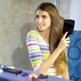 Glückliches weibliches Modell vor dem Spiegel, der langes blondes Haar bürstet stockfotografie