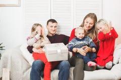 Glückliches Weihnachtsfamilie mit den Kindern, die Geschenk öffnen lizenzfreie stockfotos