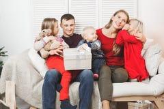 Glückliches Weihnachtsfamilie mit den Kindern, die Geschenk öffnen stockbilder
