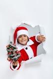 Glückliches Weihnachtsjunge, der Ihnen einen kleinen verzierten Tannenbaum gibt Stockfotografie