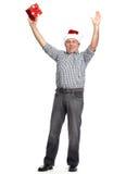 Glückliches Weihnachtsmann mit Weihnachtsgeschenk. Stockfotos