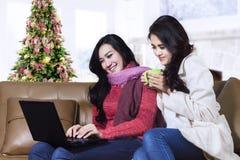 Glückliches Wintermädchen, das einen Laptop verwendet stockfotografie