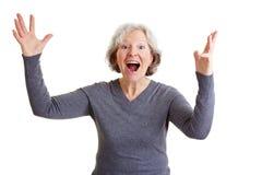 Glückliches Zujubeln der alten Frau Stockfoto