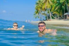 Glückporträt im tropischen Wasser: blonder Junge, der auf dem wat liegt Stockbilder
