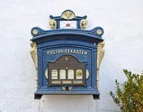 Glücksburg, Germany - April 8th, 2018 - Vintage German mailbox mounted on a whitewashed wall beside a green bush royalty free stock photo