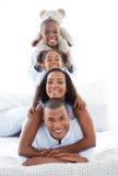 Glückselige Familie, die Spaß hat, auf Bett sich hinzulegen Lizenzfreies Stockfoto
