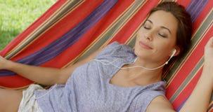 Glückseliges Entspannungsc$hören der jungen Frau Musik Stockfoto