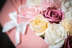 Glückwünsche auf der Geburt des Babys: Rosa Kasten mit den mehrfarbigen Blumenknospen in Form eines Babyfeldbetts lizenzfreie stockfotografie
