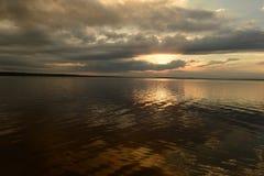 Glühen Sie in eine Wolke der Sonne im Himmel über der Oberfläche des Sees Stockfotografie