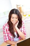 Glühende asiatische Frau, die Laptop in der Küche verwendet Stockbild