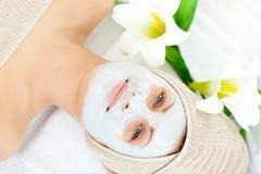 Glühende Frau mit weißer Sahne auf ihrem Gesicht Stockbild