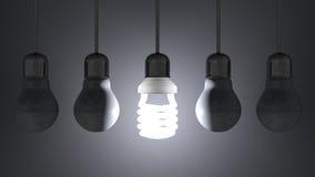 Glühende gewundene Glühlampe unter totem Wolfram eine, die am Grau hängen stock abbildung