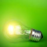 Glühende Glühlampe über grünem Hintergrund Stockfoto