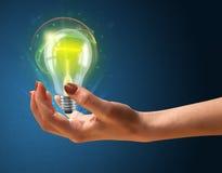 Glühende Glühlampe in der Hand einer Frau Stockfoto