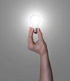 Glühende Glühlampe der Handholding Lizenzfreies Stockfoto