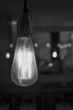 Glühende Glühlampe, die von der Decke in Schwarzweiss baumelt Lizenzfreie Stockbilder