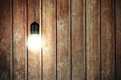 Glühende Glühlampe mit hölzerner Wand Geometrische Verzierung auf einem alten Papier Stockfoto