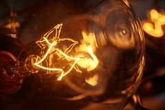 Glühende Glühlampe und glühende Glühlampen im Hintergrund stockfotos