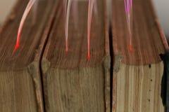 Glühende Glasfaserkabel angeschlossen mit alten Büchern Stockfotografie