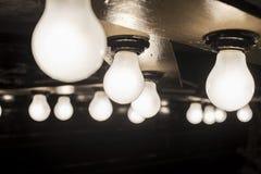 Glühende Lampe auf Holzfuß Stockfotos