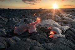 Glühende Lavaflüsse unter schönen Sonnenunterganghintergrund stockfoto