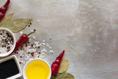 Glühende Paprikapfeffer-Hülsenerbsen, Salz, Öl, Schwarzkümmelsamen und Lorbeerblätter auf grauer Weinlese asphaltieren kulinarisc Stockfotografie