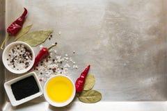 Glühende Paprikapfeffer-Hülsenerbsen, Salz, Öl, Schwarzkümmelsamen und Lorbeerblätter auf grauer Weinlese asphaltieren kulinarisc Stockbilder