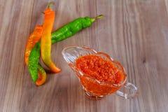 Glühende Paprikapfeffer und Salsa oder adjika in der weißen Schüssel Lizenzfreies Stockbild