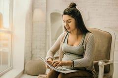Glühende schwangere Frau, die ihre Doktorverordnungen studiert lizenzfreie stockfotografie