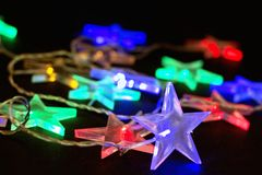 Glühende Weihnachtsgirlande von Sternen auf einem schwarzen Hintergrund stockfoto
