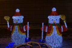 Glühende Zahlen von Girlanden in Form Santa Clauss und eines Schneemannes mit einem Buchstaben, am Vorabend des Weihnachten Lizenzfreie Stockbilder