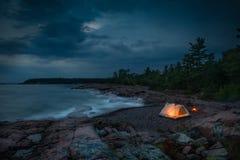 Glühender Campingplatz durch das Wasser Stockfotos